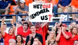 An Arkansas State University fan holds a sign asking if Gus Malzahn remenbers thems.